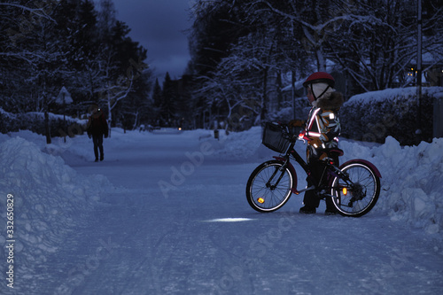 Obraz Girl on a bicycle in a winter evening. Light is reflected from clothing reflectors and bicycle wheels. Safe cycling in the dark time. - fototapety do salonu