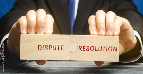 Man holds wooden puzzles with the words Dispute Resolution Wallpaper Mural