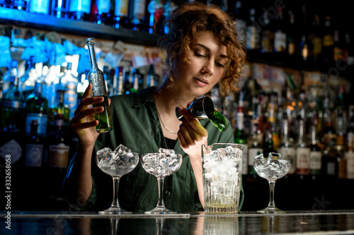 Fototapeta young woman bartender pours green drink into large glass used beaker. obraz