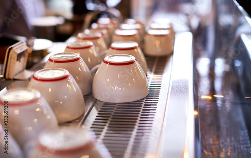 Obraz Close Up Of Cups Arranged On Machine In Coffee Shop - fototapety do salonu
