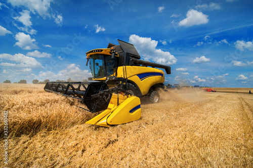 Leinwand Poster combine harvester harvesting cereals, sky with beautiful clouds