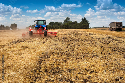 Fototapeta blue new tractor pulls a red harrow in the field, soil preparation