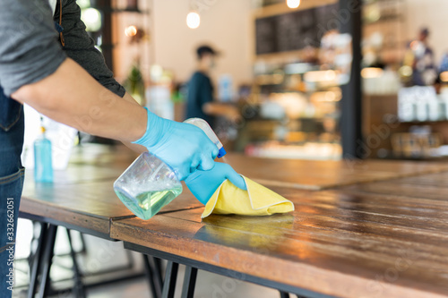 Obraz Waiter cleaning the table with disinfectant spray and microfiber cloth in cafe. - fototapety do salonu