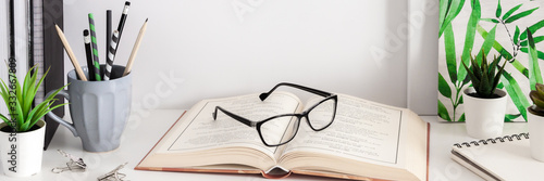 School desk on a white wall. School supplies, mug with pencils, books and notebooks, plants. Copy space. Open book with glasses.Panorama