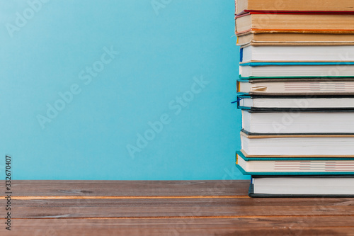 Photo A simple composition of many hardback books, raw books on a wooden table and a bright blue background