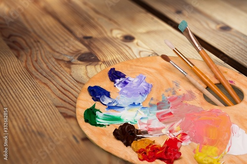 Fototapeta Wooden art palette with blobs of paint and  brushes on desk