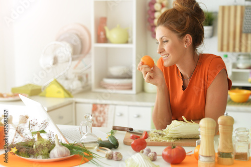 Fototapeta Portrait of beautiful young woman cooking in kitchen
