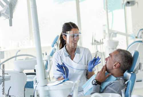 Fotomural Dentist in dental office talking with male patient and preparing for treatment