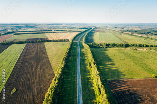 Obraz Country road and green agricultural fields at sunset, panoramic aerial view. Rural landscape in Penza Oblast, Russia - fototapety do salonu