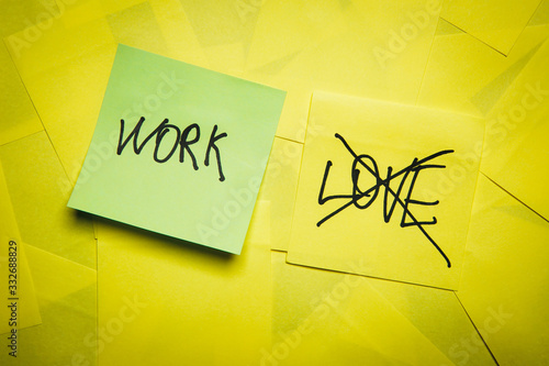 Green sticky note with words work and crossed love on yellow notes