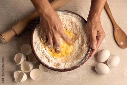 Photo manos amazando harina y huevo en un cuenco de madera