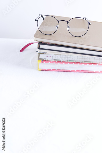 Photo Stack of note books for notes and annotations with glasses on the top on a white table