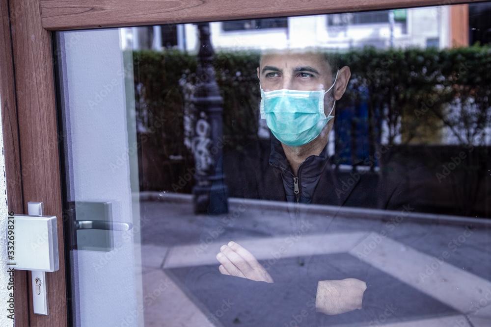 Fototapeta uomo con mascherina guarda il mondo attraverso un vetro non potendo uscire per le restrizione a causa della pandemia