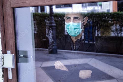 Photo uomo con mascherina guarda il mondo attraverso un vetro non potendo uscire per l