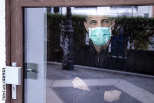 Fotografía uomo con mascherina guarda il mondo attraverso un vetro non potendo uscire per l