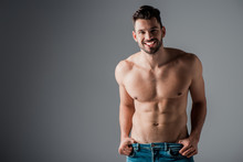 Smiling Muscular Sexy Shirtless Man In Jeans On Grey