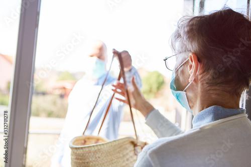 Fototapeta Seniorin in Quarantäne bekommt Lebensmittel Lieferung obraz