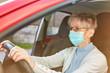Seniorin mit Mundschutz beim Auto fahren