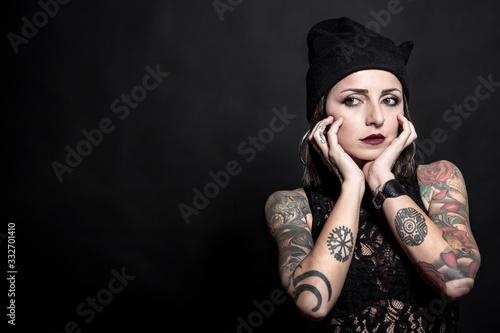 bella ragazza tatuata con cuffietta nera, si pota le mani al mento, isolata su s Wallpaper Mural