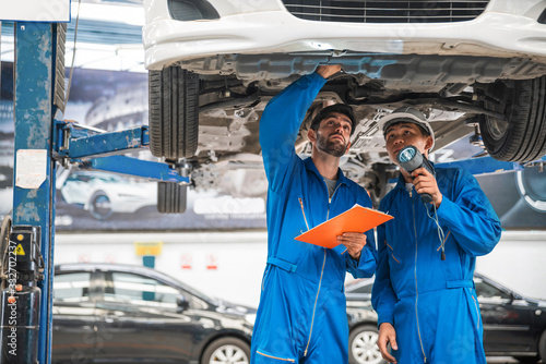 Photo Mechanic in blue work wear uniform inspects the car bottom with his assistant