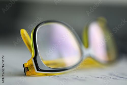 Photo Yellow plastic eyeglasses lying at worktable