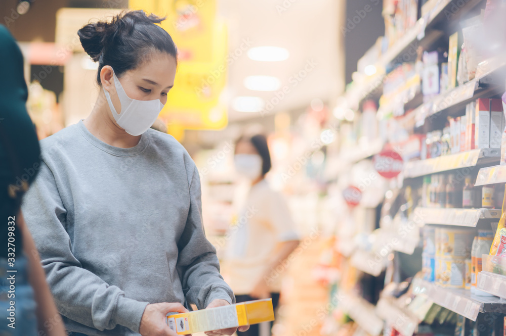 Fototapeta Asian woman wearing a mask in the supermarket, Panic shopping during Coronavirus covid-19 pandemic.Budget buying at a supply store.Buying freezer smart purchased household pantry groceries