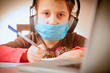 Coronavirus and quarantine concept. Close up young beautiful girl in face medicine mask studying remotely at home.