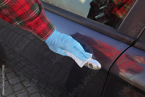 Obraz Human hand in protective gloves  cleaning car door handle using antibacterial or cleaning solution and wet wipes - fototapety do salonu