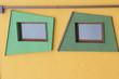 Leinwanddruck Bild - Fenster mit grüner Umrahmung auf gelber Wand mit Fallrohr