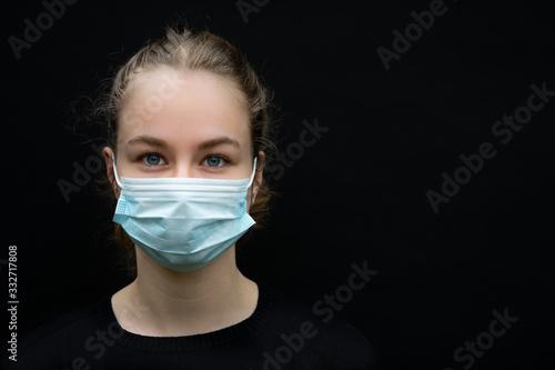 une jeune femme, blonde, avec un masque chirurgicale de protection Wallpaper Mural