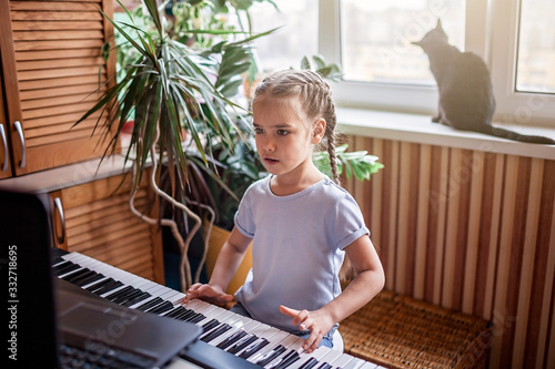 Photo Young musician playing classic digital piano at home during online class at home