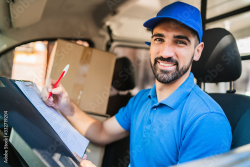 Foto Delivery man checking delivery list in van.