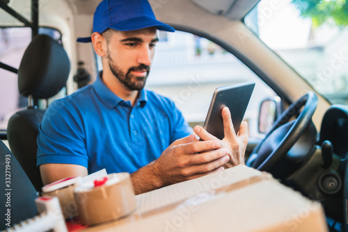 Delivery man driver using digital tablet. Fototapeta