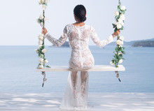 Back View Of Beautiful Woman In White Lace Dress Posing On The Outdoor Swing With Flowwers Over Sea And Sky Background