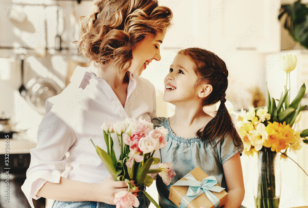 Fototapeta happy mother's day! child daughter gives flowers for  mother on holiday