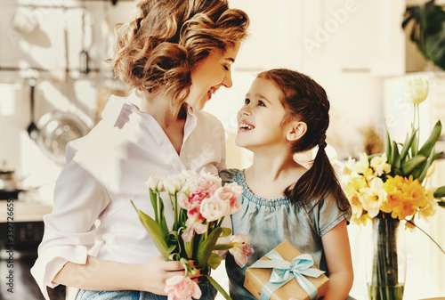 happy mother's day! child daughter gives flowers for  mother on holiday
