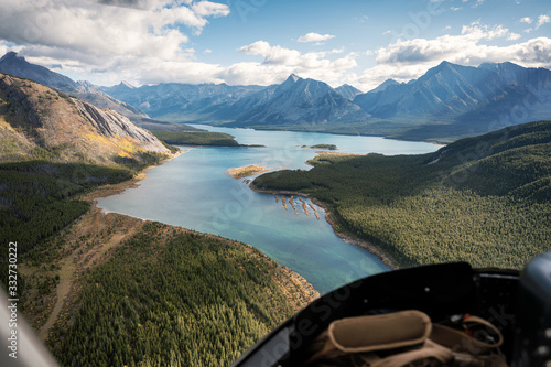 Inside of helicopter flying on rocky mountains with colorful lake Fototapet