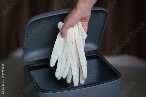 Fototapeta Hand putting used dirty surgical glove to  a garbage bin. Mask protect dust and corona virus in trash. obraz