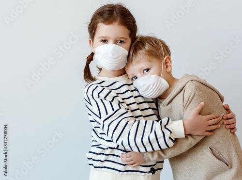 Fotografia, Obraz Little siblings in medical masks embracing each other.