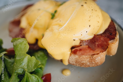 benedict egg with bacon and salad on the white plate Wallpaper Mural