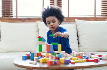 Happy African American Cute Little Child Boy Play With Wooden Blocks Construction On The Table At Home. Learning Creative Concept