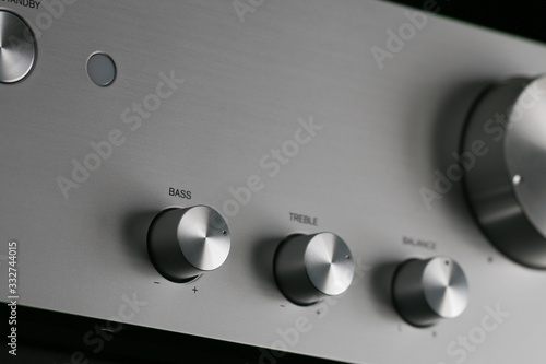 Photo Close-up of Control Knobs on a Silver Metallic Amplifier