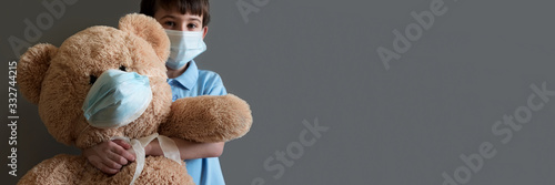 Banner 3:1. COVID-19 quarantine. Boy and teddy bear wearing protective mask on gray background. Selective focus. Flu, illness, pandemic concept