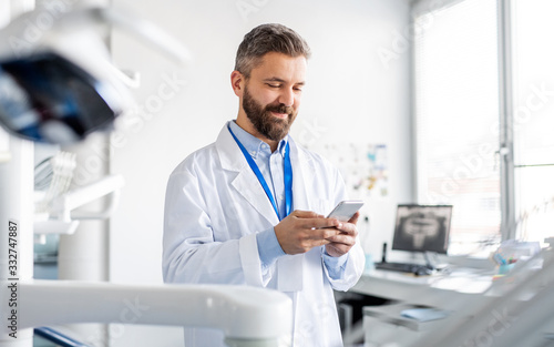 Dentist in modern dental surgery, using smartphone.