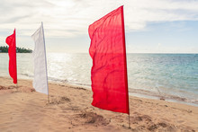 Red And White Flags On The Bea...