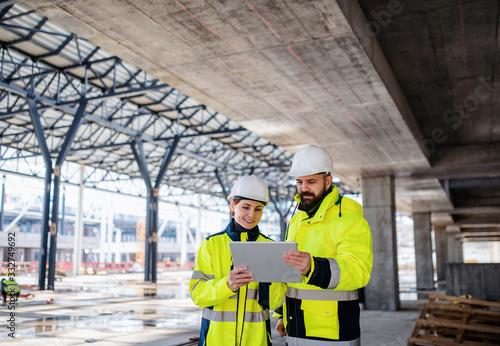 Obraz Engineers standing outdoors on construction site, using tablet. - fototapety do salonu