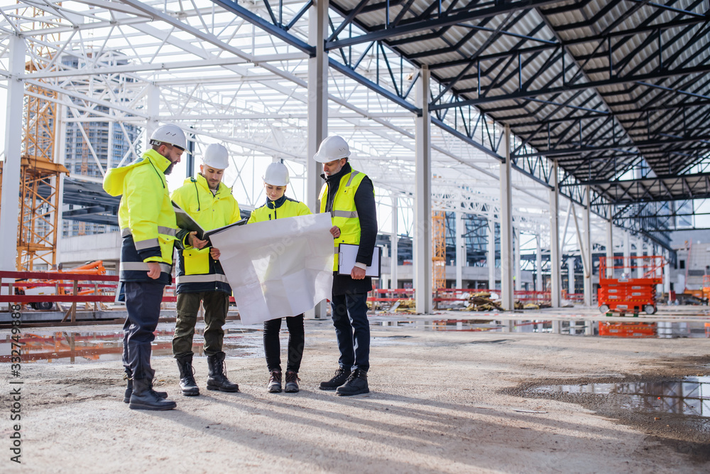 Fototapeta Group of engineers with blueprints standing on construction site.