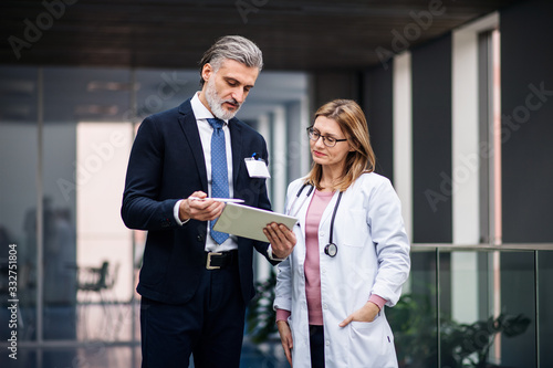 Pharmaceutical sales representative with tablet talking to doctor.