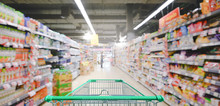 Supermarket Aisle With Empty Green Shopping Cart