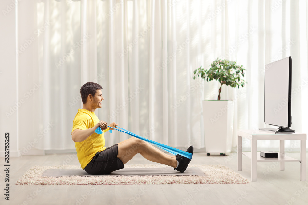 Fototapeta Man exercising with an elastic band in front of a TV at home